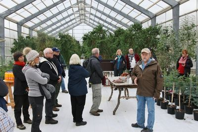 During an excursion, PhD Thröstur Eysteinsson, head of Icelandic Forest Service (facing at right), presented the indoor seed orchard at Vaglir with ongoing tree breeding and seed production projects